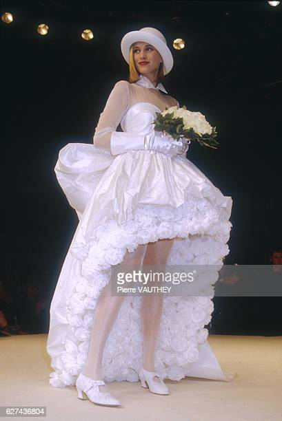 A fashion model wears a white haute couture wedding dress and brimmed hat by French fashion designer Lolita Lempicka She modeled the dress during the...