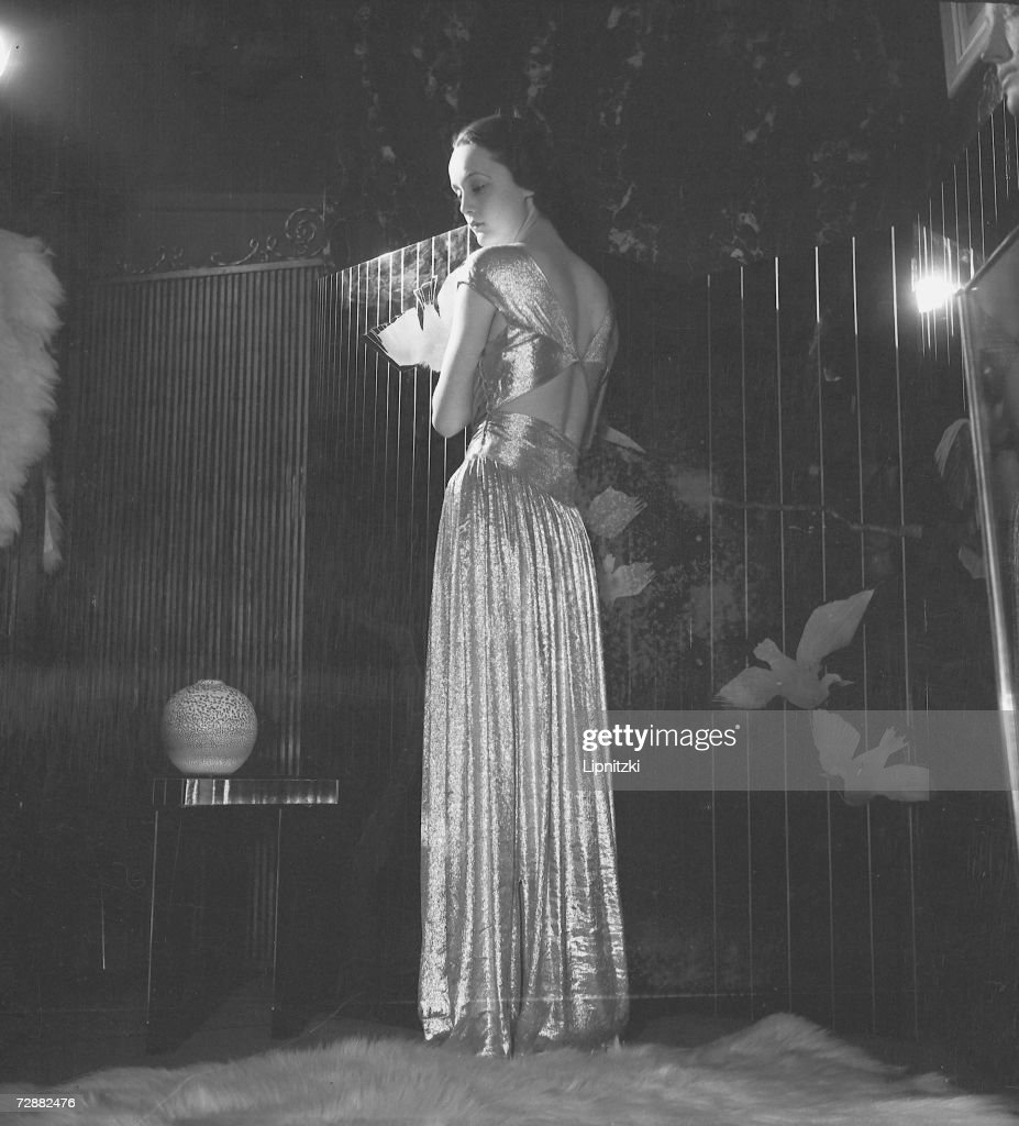 A fashion model wears an evening gown designed by French fashion designer Jeanne Lanvin, Paris, February 1935.