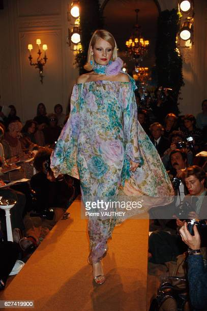 A fashion model wears an offtheshoulder floral print haute couture cocktail dress by French fashion designer Marc Bohan for the Christian Dior...