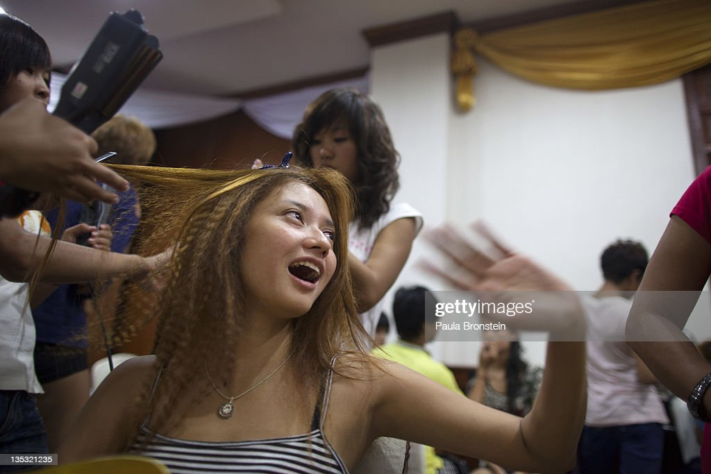 Fashion models get their hair done as dozens get ready backstage for a fashion show featuring OPT jeans December 8, 2011 in Yangon, Myanmar. The pace of change in Myanmar brought U.S Secretary of State Hillary Clinton to the country where she discussed further paths to reform and crucial talks with both Aung San Suu Kyi and the highest levels of the Burmese government. For many years Myanmar has suffered from economic stagnation, political repression and international isolation. In March the army handed power to a civilian government after almost five decades of the military regime's strong arm rule. The handover took place after a controlled election under a new constitution that preserved much of the military clout. Internet has been loosened up as previously inaccessible foreign news and opposition websites have been unblocked.