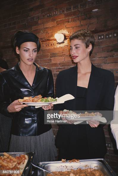 Fashion models Linda Evangelista and Christy Turlington help themselves to a buffet in Tribeca New York City circa 1992