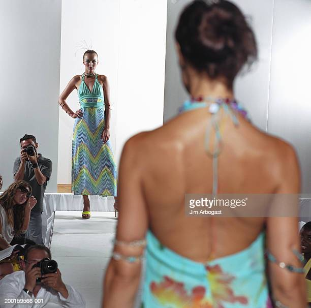 Fashion models walking on catwalk (focus on woman in background)