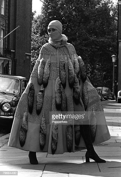 A beige Swakara cape of suede and sheepskin with fox collar and tails modeled in London 29 September