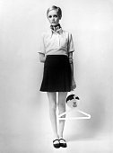 1967 British model Twiggy wearing a yellow blouse and navy mini skirt