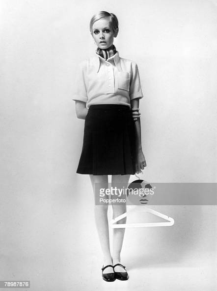 1967 British model Twiggy wearing a yellow blouse and navy mini skirt