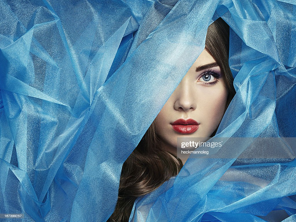 Fashion photo of beautiful women under blue veil : Stock Photo