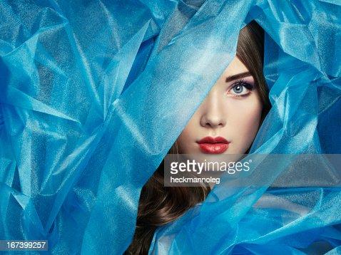 Fashion photo of beautiful women under blue veil : Stockfoto