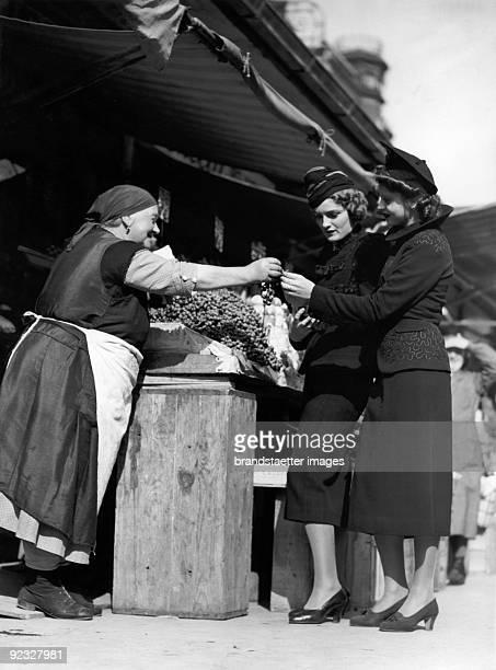 Fashion photography At a fruit and veg stall Naschmarkt Vienna Photograph Around 1936