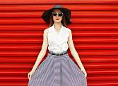 Fashion portrait of beautiful woman wearing a black straw hat, sunglasses showing striped skirt over red background