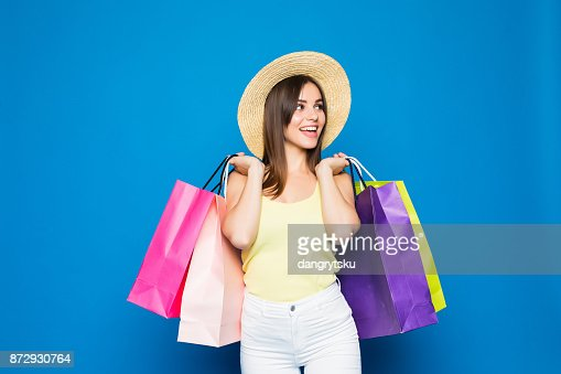 Fashion portrait young smiling woman wearing a shopping bags, straw hat over colorful blue background : Stock Photo