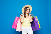 Fashion portrait young smiling woman wearing a shopping bags, straw hat over colorful blue