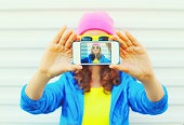 Fashion pretty cool girl taking photo self portrait on smartphone over white background wearing colorful clothes and sunglasses