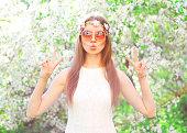 Fashion pretty cool hippie girl having fun over flowering garden background