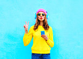 Fashion pretty sweet carefree woman listening music in headphones with smartphone wearing a colorful pink hat yellow sweater sunglasses over blue background