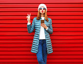 Fashion pretty woman using smartphone holds in hands on a red background in the city