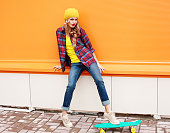 Fashion pretty woman wearing casual colorful clothes with skateboard in the city