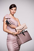 Beautiful glamour woman with jewellery posing with clutch and bag in elegant dress. Fashion girl deciding between clutch bag and purse isolated on grey backgound. Elegant woman with choosing her bag f