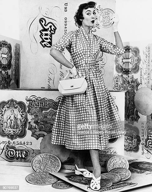 Fashion shot of a woman with large cardboard pieces of imperial coinage and banknotes