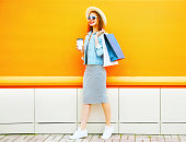 Fashion smiling woman holds a coffee cup, shopping bags wearing a straw hat on orange background