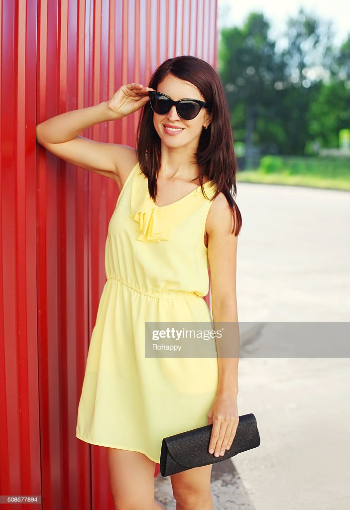 Fashion smiling woman wearing dress and sunglasses with handbag clutch : Stockfoto