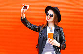 Fashion pretty smiling young woman taking picture self portrait on smartphone in black rock style over city red background