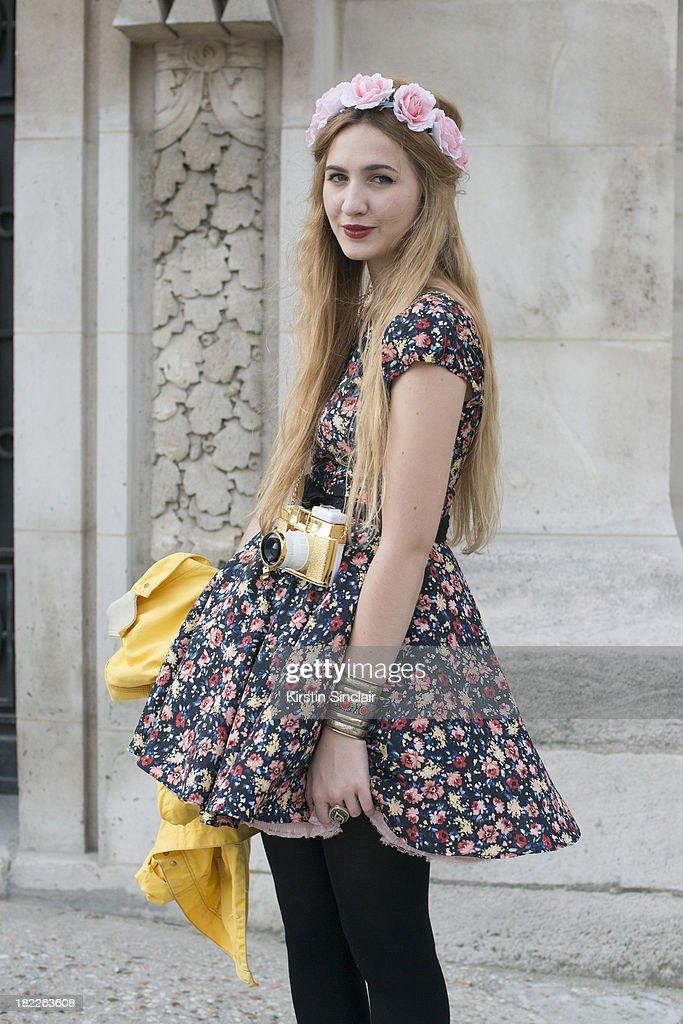 Fashion student Elisa Baudoin wears a Zara dress, Asos headpiece and a Dianna F camera on day 5 of Paris Fashion Week Spring/Summer 2014, Paris September 28, 2013 in Paris, France.