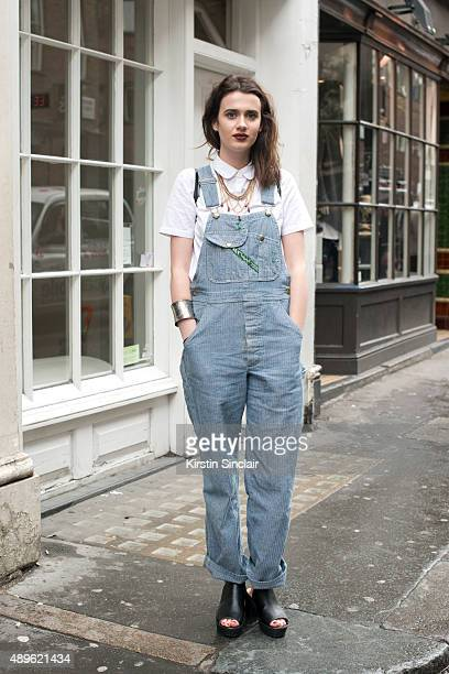 Fashion student Olivia Miller wears Pop Boutique vintage dungarees and Topshop top bracelet and shoes on day 5 during London Fashion Week...
