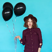 Beautiful fashion young woman holding black balloons and wearing stylish clothes isolated on blue background