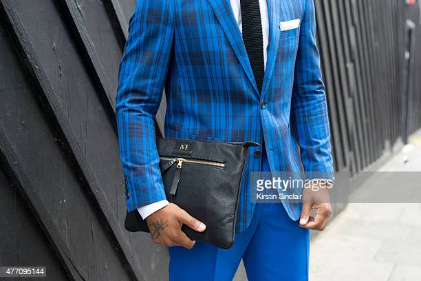 Fashion Stylist and Designer Dejon Marquise wears a Dejon Marquise suit bag and belt Zara tie and H and M shirt on day 2 of London Collections Men on...