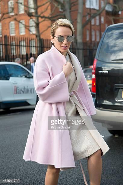 Fashion stylist Aram Kabbani wears a Max Mara coat Dior bag Dior Glasses and Topshop unique dress on February 24 2015 in London England