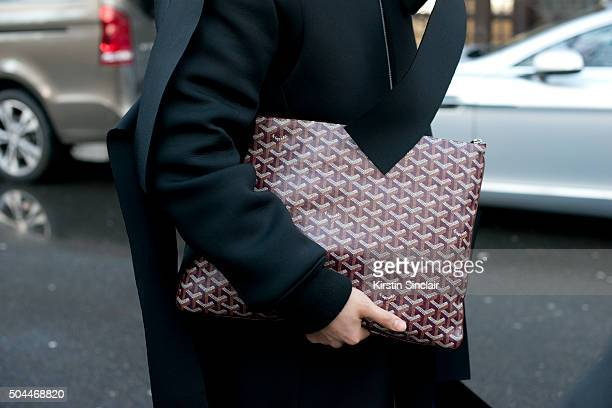 Fashion stylist Gareth Chow wears a Nicole Panda coat Wanhung trousers and Goyard bag on day 1 of London Collections Men on Januay 8 2016 in London...