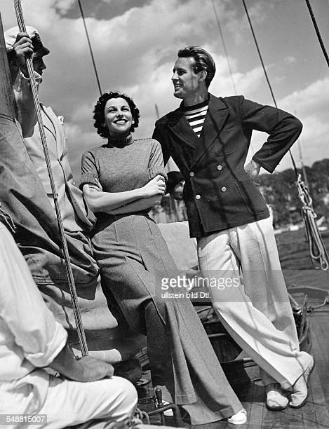 Woman and man on a sailboat she wearing elegant jersey pants and a handknit sweater with turtle neck collar he wearing a doublebreasted jacket and...