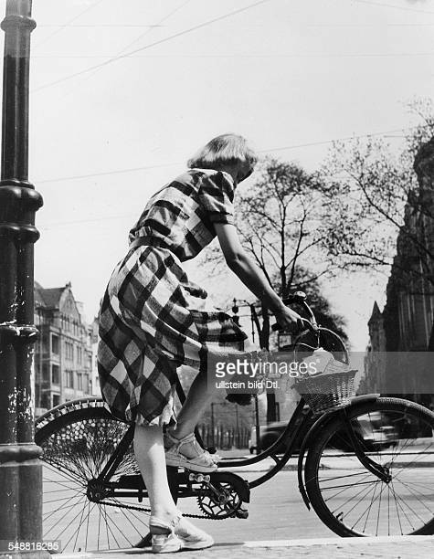 woman in a checked overall with baggy trouserswith her bicycle 1949 Photographer Sonja Georgi Published by 'Erika' 20/1940 Vintage property of...