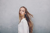 Fashion teenager girl with blowing hair standing against blue textured wall background. Trendy young teen woman in white shirt posing indoors and looking at camera