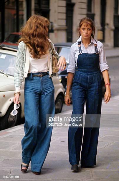 Fashion The Blue Jeans France 1973 L'empire du bluejean Deux jeunes femmes côte à côte sur un trottoir portent l'une un bluejeans l'autre une...