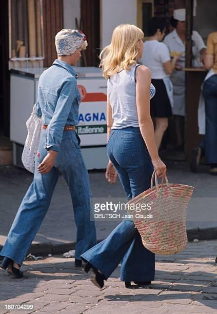 Fashion The Blue Jeans France 1973 L'empire du bluejean Deux jeunes femmes se déplacent côte à côte dans une rue l'une vêtue d'une chemise jean sur...