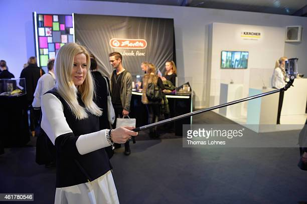 A fashion visitor takes a picture of herself with a selfie stick during the MercedesBenz Fashion Week Berlin Autumn/Winter 2015/16 at Brandenburg...