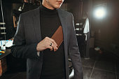 A stylish man in a suit puts a leather purse in his jacket pocket