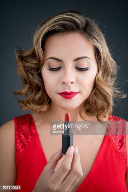 Fashion woman applying red lipstick