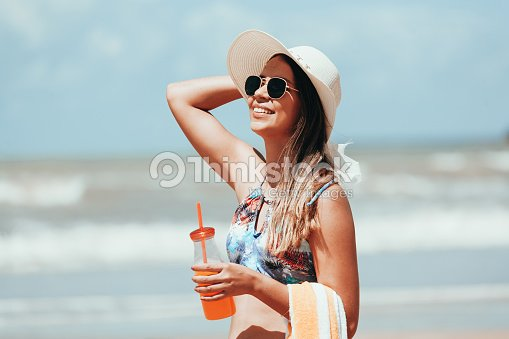 Fashion woman drinking cocktail on the beach : Foto de stock