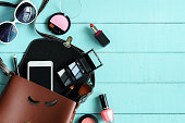 Fashion woman essentials, cosmetics, cellphone, makeup accessories on wooden background, Top view