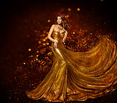 Fashion Woman Gold Dress, Luxury Girl in Elegant Golden Fabric Gown, Flying Sparkles Cloth