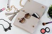 Fashion woman handbag with cellphone, makeup and accessories, Top view