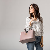 Young glamour woman wearing polka dot shirt and jeans posing with pink handbag. Beautiful stylish girl holding bag and looking away with copy space. Fashion woman holding peach bag with sunglasses on