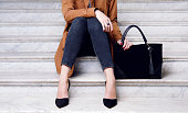 Close up fashion woman sitting in high heels shoes hold black big handbag . Stylish outfit jeans and coat