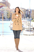 Full body front view of a fashion woman walking towards camera and using smart phone watching media content on line or texting