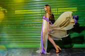 side view of fashion woman walking with flying dress,