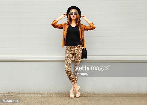 Fashion woman wearing hat, sunglasses, jacket, handbag posing in city : Stock Photo