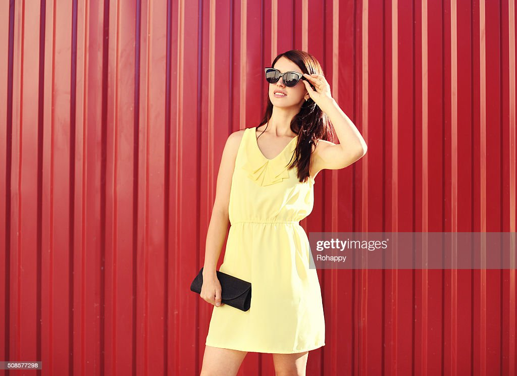 Fashion woman wearing yellow dress and sunglasses with handbag clutch : Stock Photo