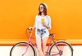 Fashion pretty woman with coffee or juice cup and retro vintage bicycle over colorful orange background